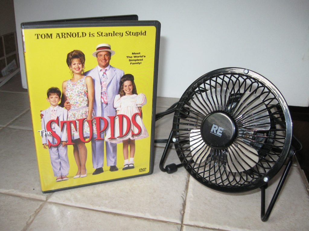 """a small fan next to a dvd copy of """"the Stupids"""""""